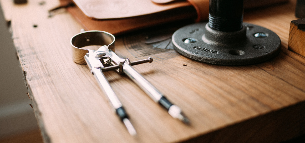 Image includes a compass atop a wooden desk.